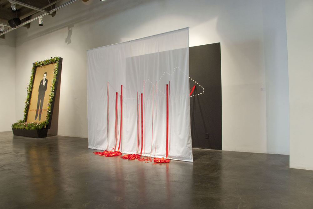 Bloodlines, an installation comprised of ribbon, wall, and scrim
